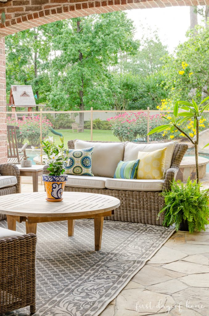 Outdoor patio set with blue and yellow pillows and teak accent furniture