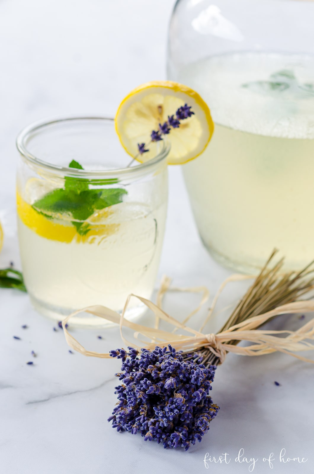 Lavender stems bunched together with lavender lemonade and slices of fresh lemon