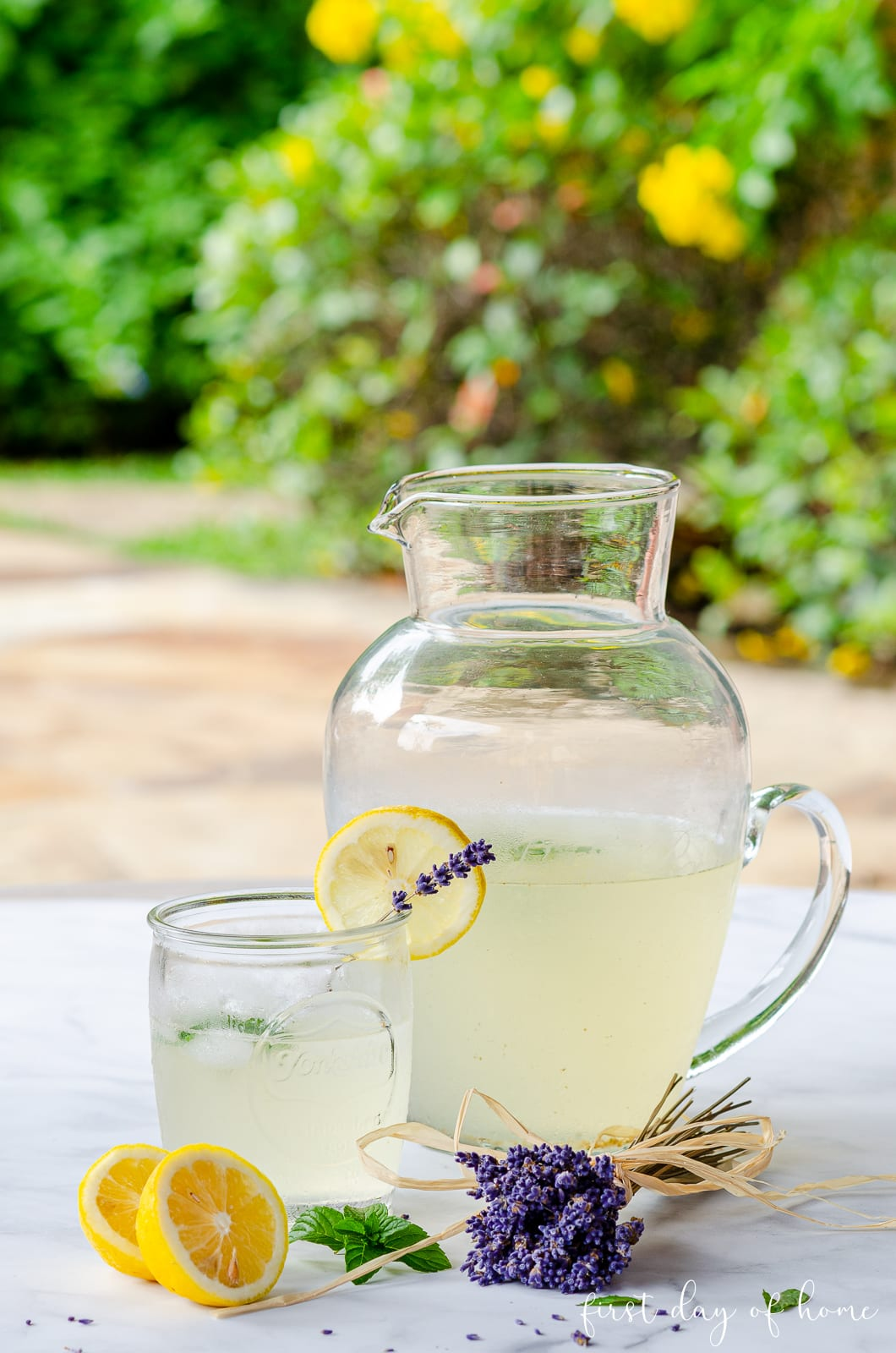 Lavender lemonade in pitcher and garnished with dried lavender stems and lemon slices with mint sprigs