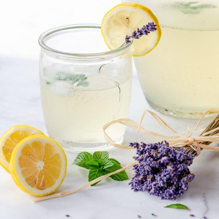 Lavender lemonade in mason jar glass with lemon halves and dried lavender stems