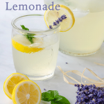 Lavender lemonade served in mason jar cup with garnish of lemons, mint and lavender stems