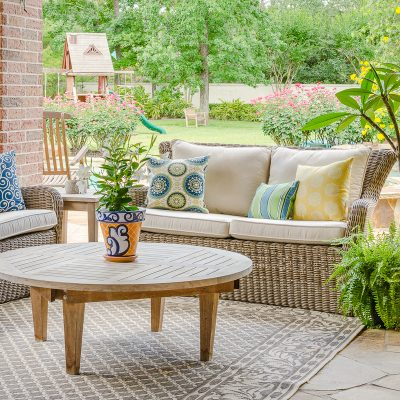Outdoor decor with blue and yellow color scheme, teak furniture, woven outdoor seating and flowering plants