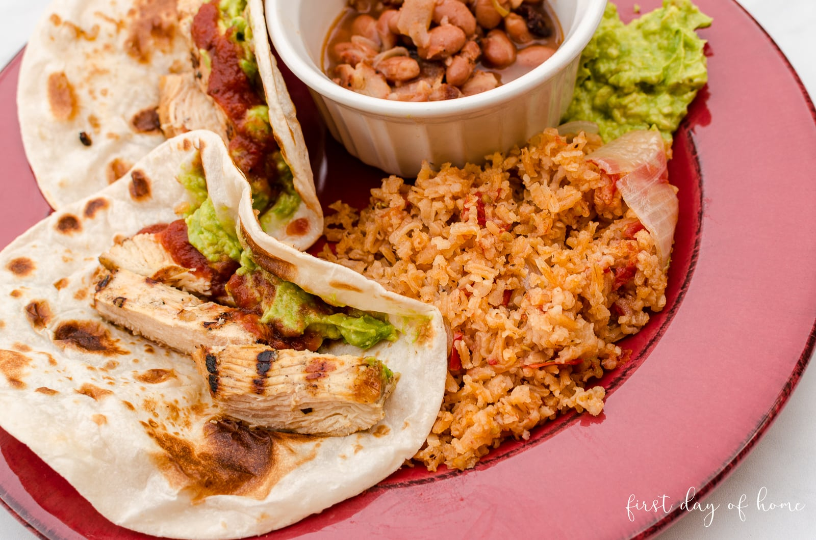 Spanish rice served with charro beans, flour tortillas and chicken fajitas