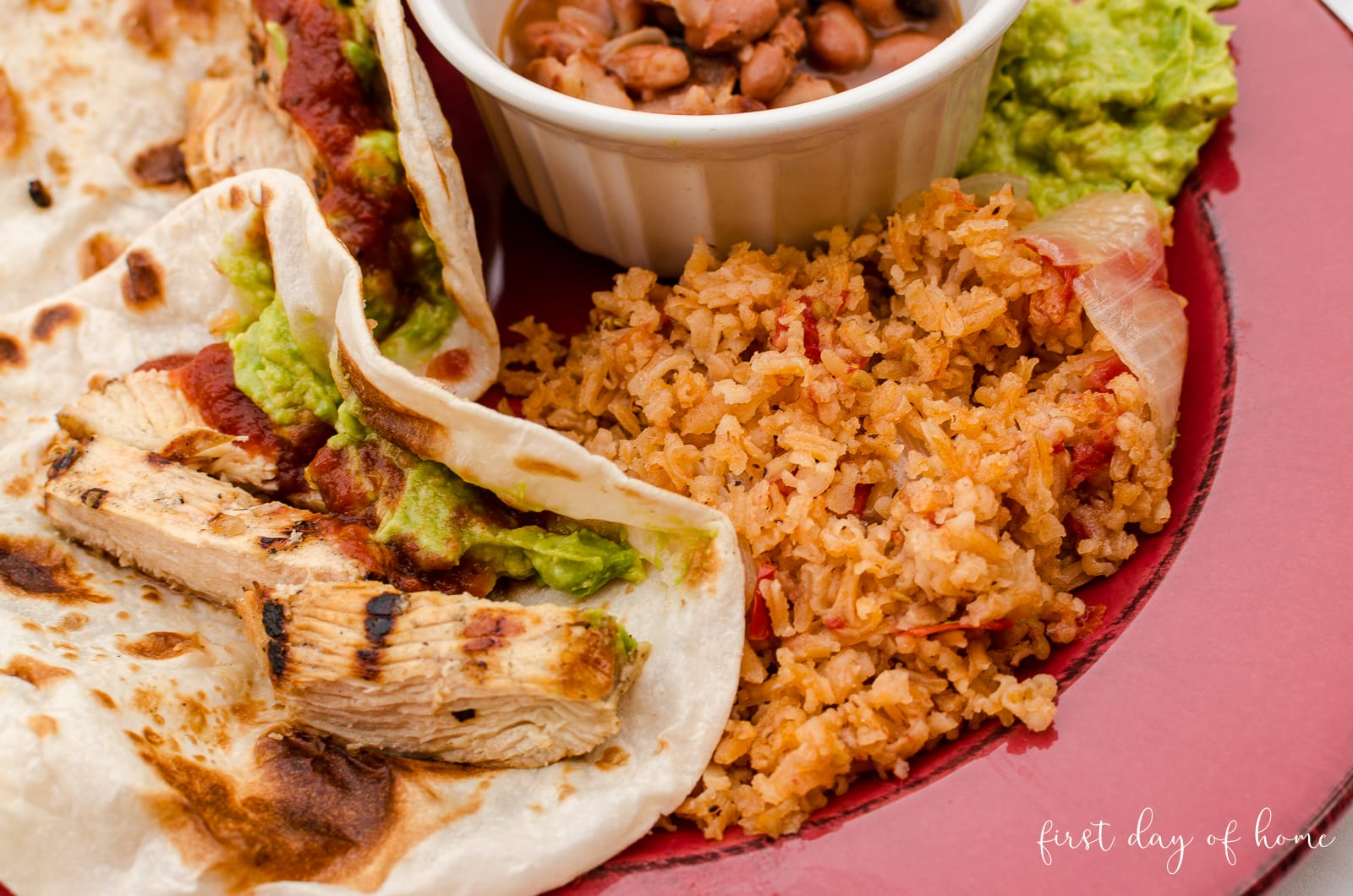 Close up of Spanish rice on plate with chicken fajita tacos and charro beans