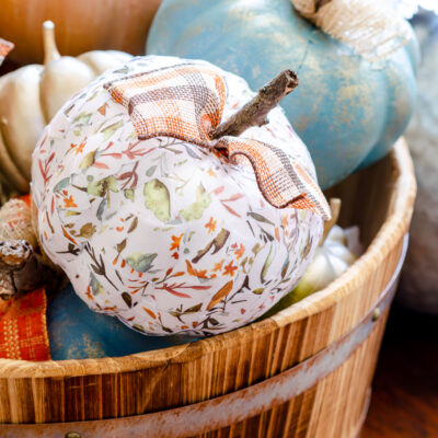 Decoupage pumpkin made with scrapbook paper and Mod Podge with farmhouse ribbon and natural stem