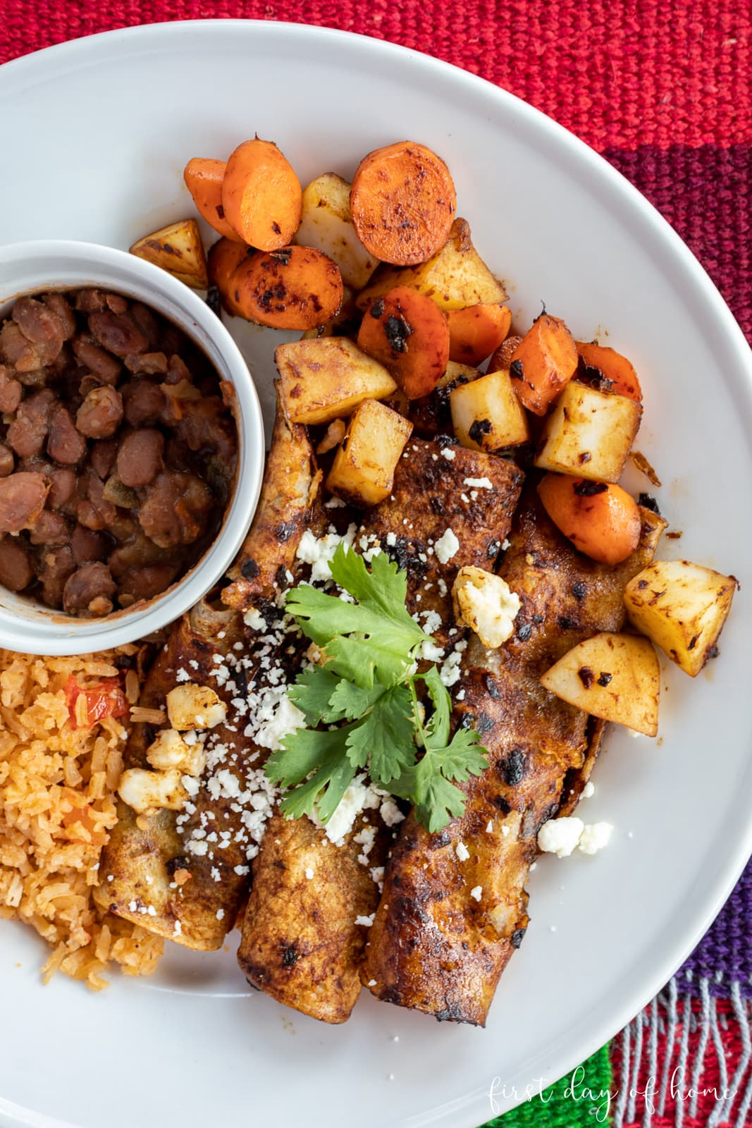 Red enchiladas (enchiladas rojas) served with diced carrots and potatoes, charro beans and Spanish rice