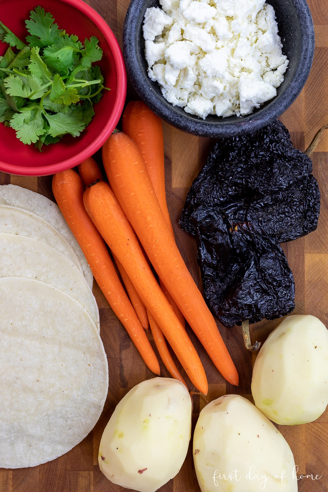 Ingredients for red enchiladas, including corn tortillas, queso fresco, carrots, red potatoes, and ancho chiles