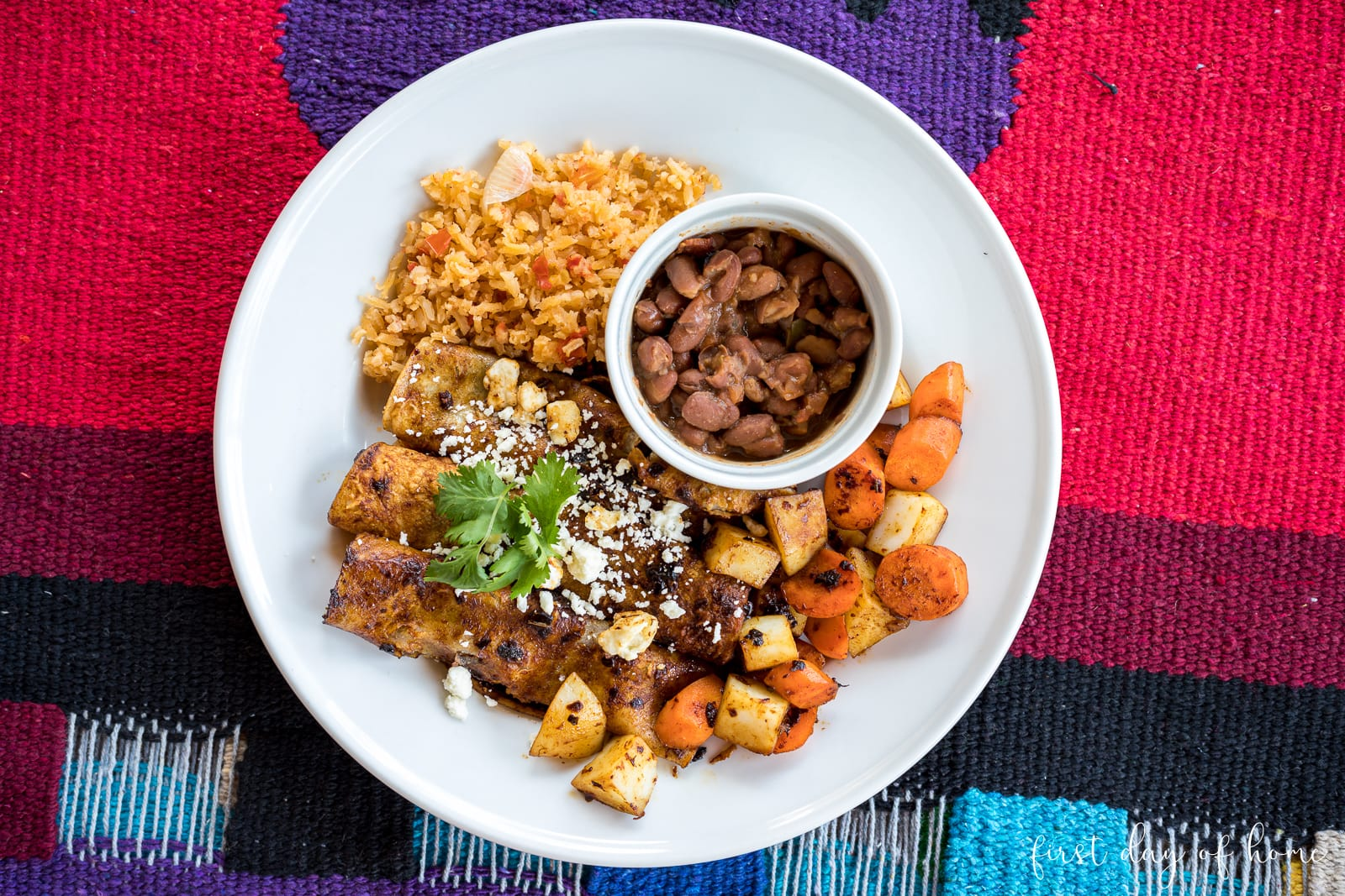 Red enchiladas topped with queso fresco cheese and cilantro, served with sides of diced potatoes/carrots, rice and beans