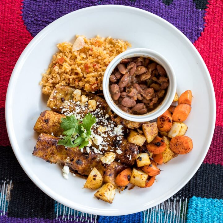 Red enchiladas served with diced carrots and potatoes and sides of borracho beans and Spanish rice