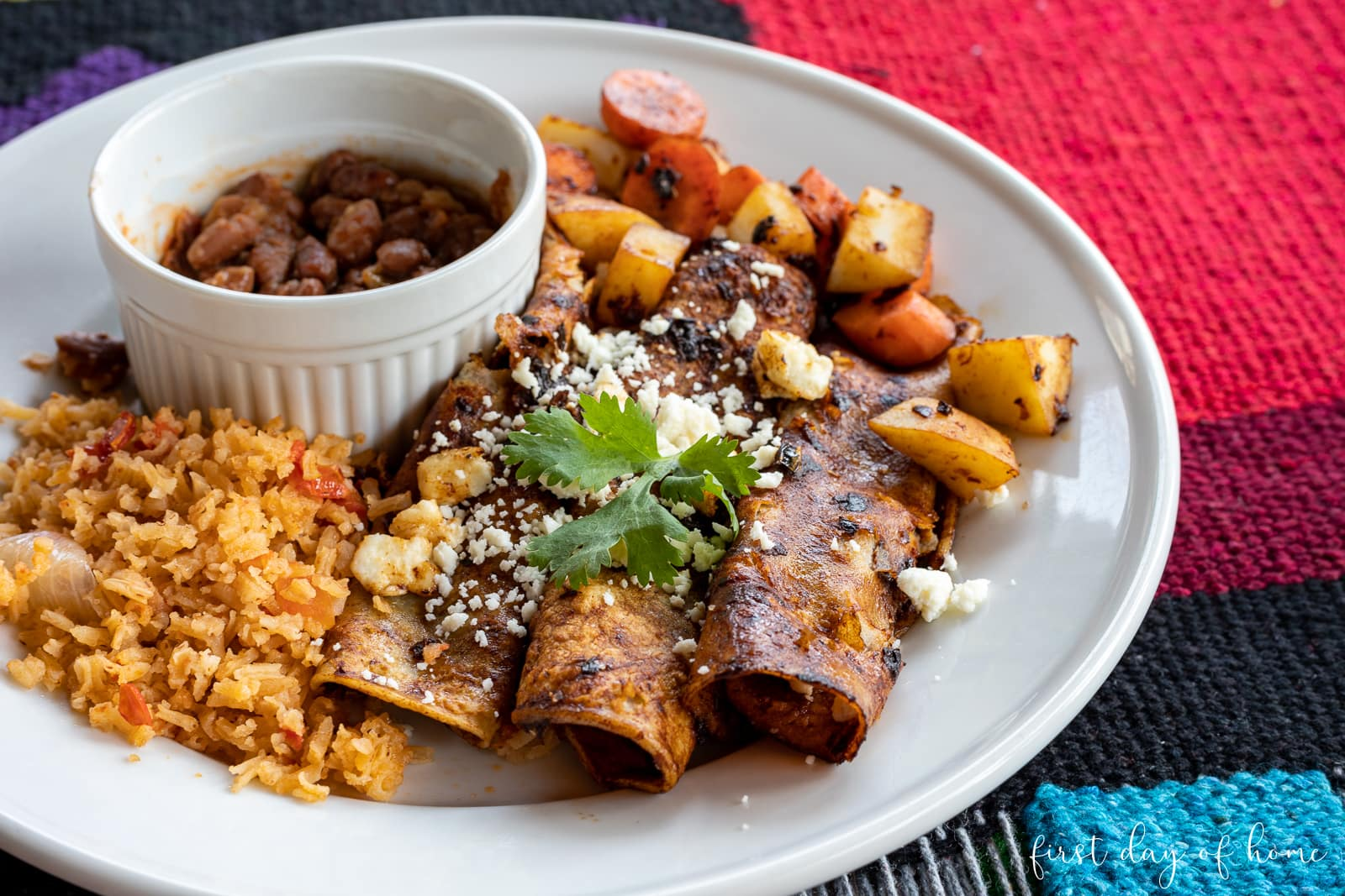 Enchiladas rojas or red enchiladas served with Spanish rice (Mexican rice) and charro beans