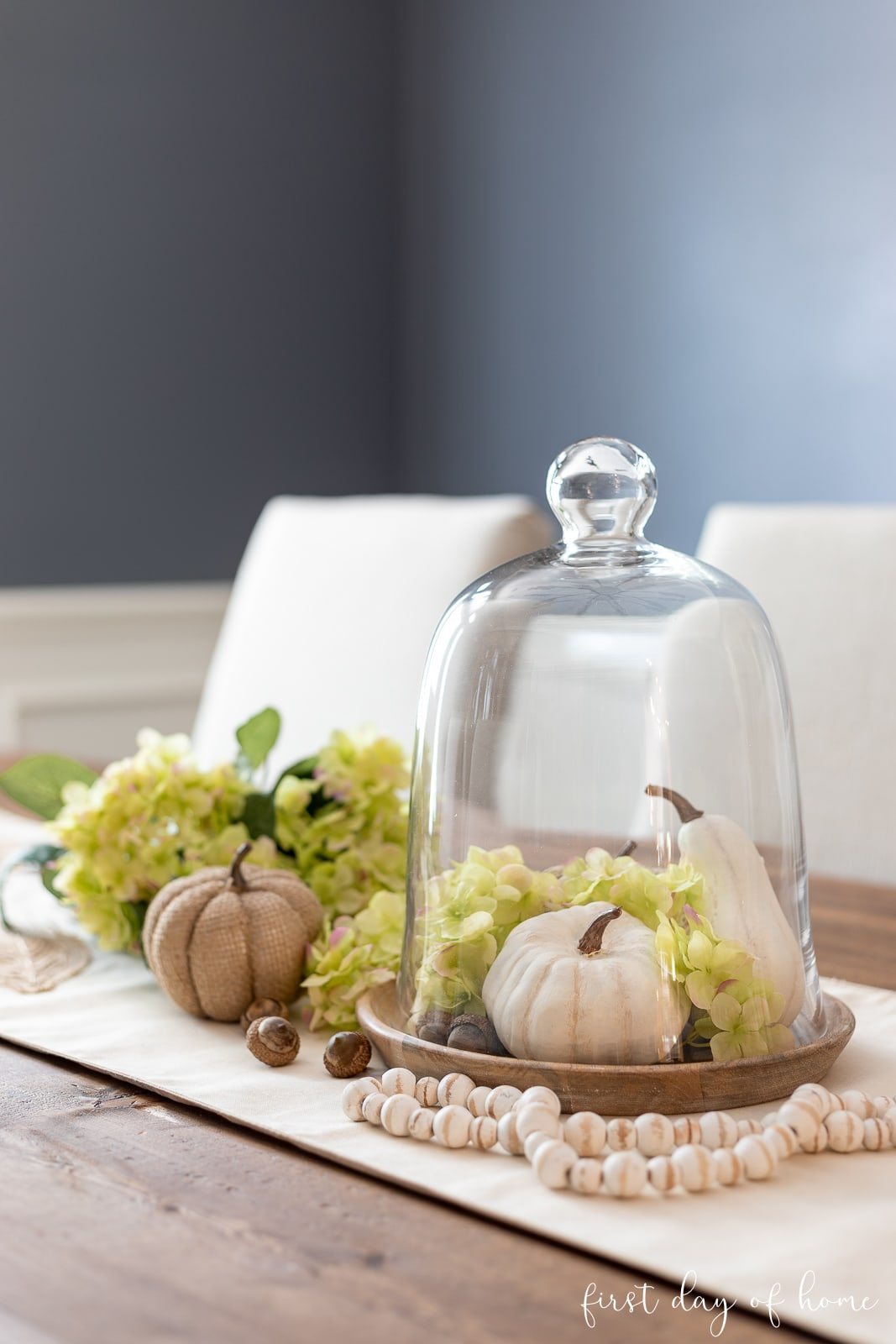 DIY fall centerpiece with glass cloche, hydrangeas, DIY baby boo white pumpkins, acorns and neutral table runner