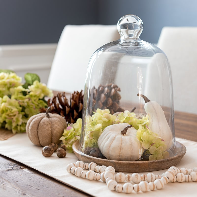 Fall cloche with white pumpkins, green hydrangeas and wooden bead garland
