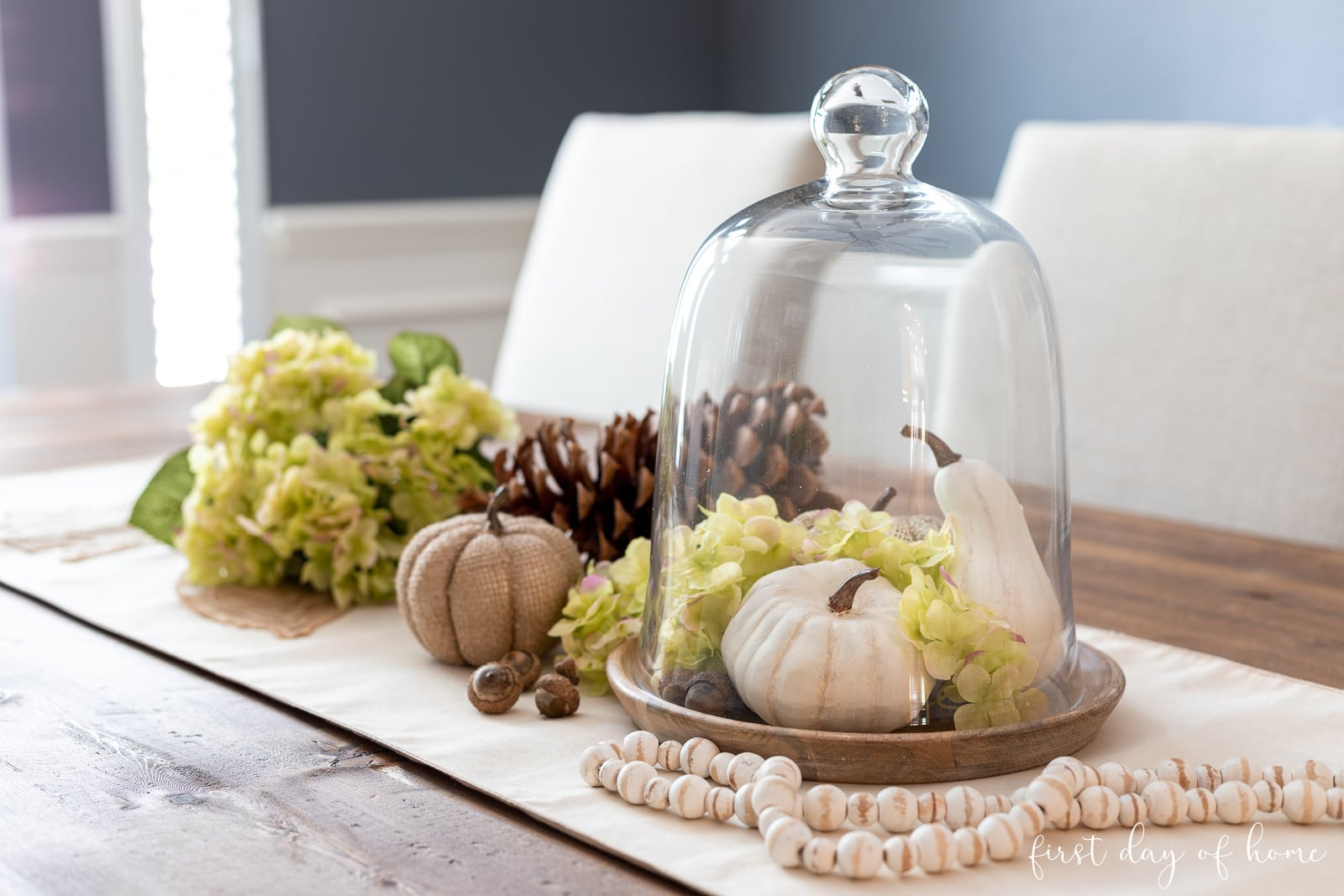 Fall centerpiece with faux white pumpkins, glass cloche, green hydrangeas and wood bead garland.