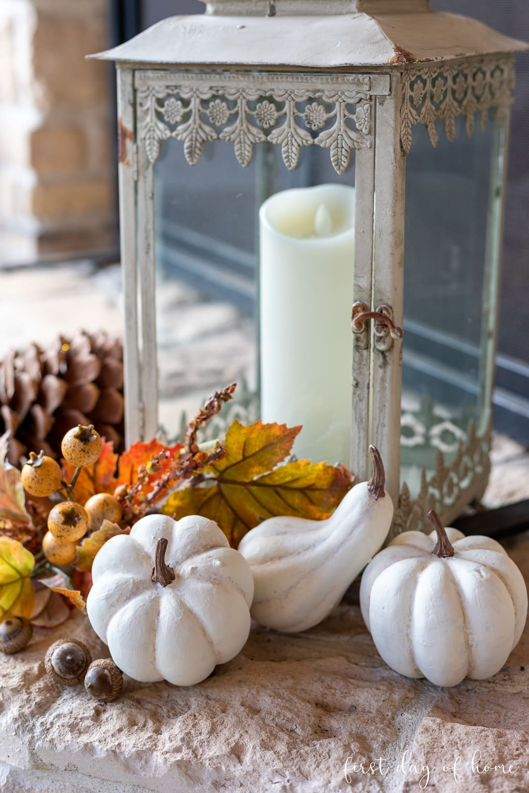 White painted pumpkins by lantern with fall leaves and pinecones