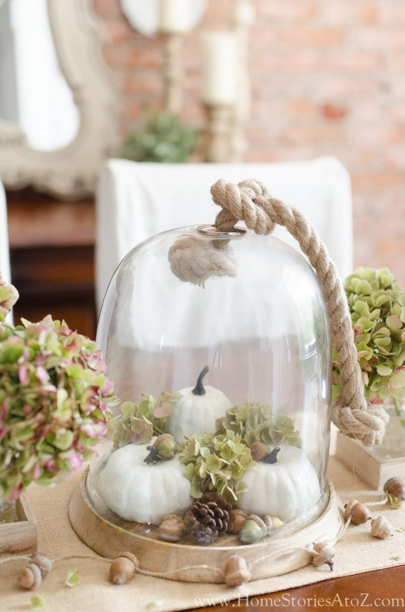 Fall cloche with white baby boo pumpkins, green hydrangeas and an acorn garland, by Home Stories A to Z blog