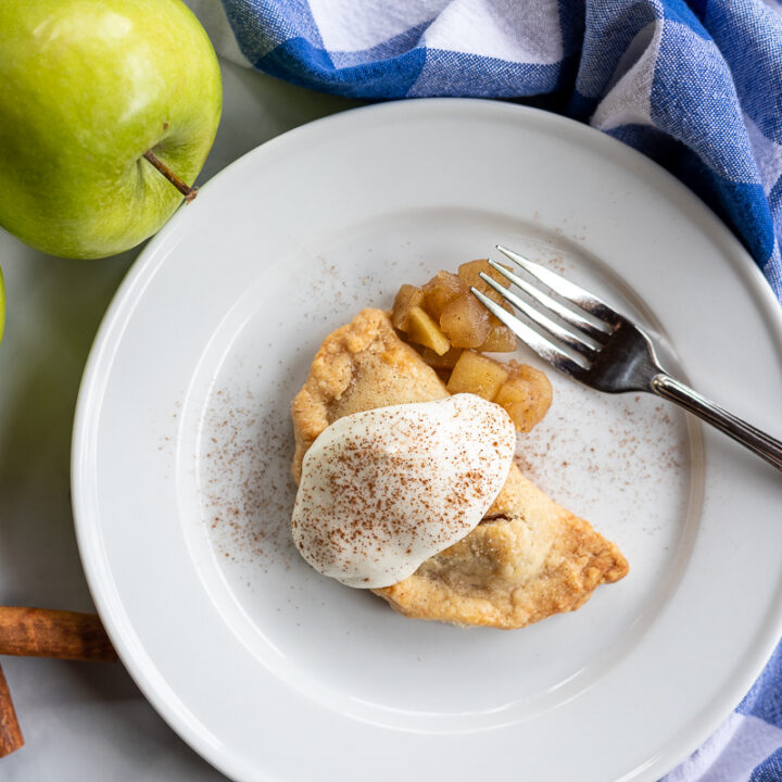 Baked apple empanadas with whipped cream and cinnamon sprinkles on top