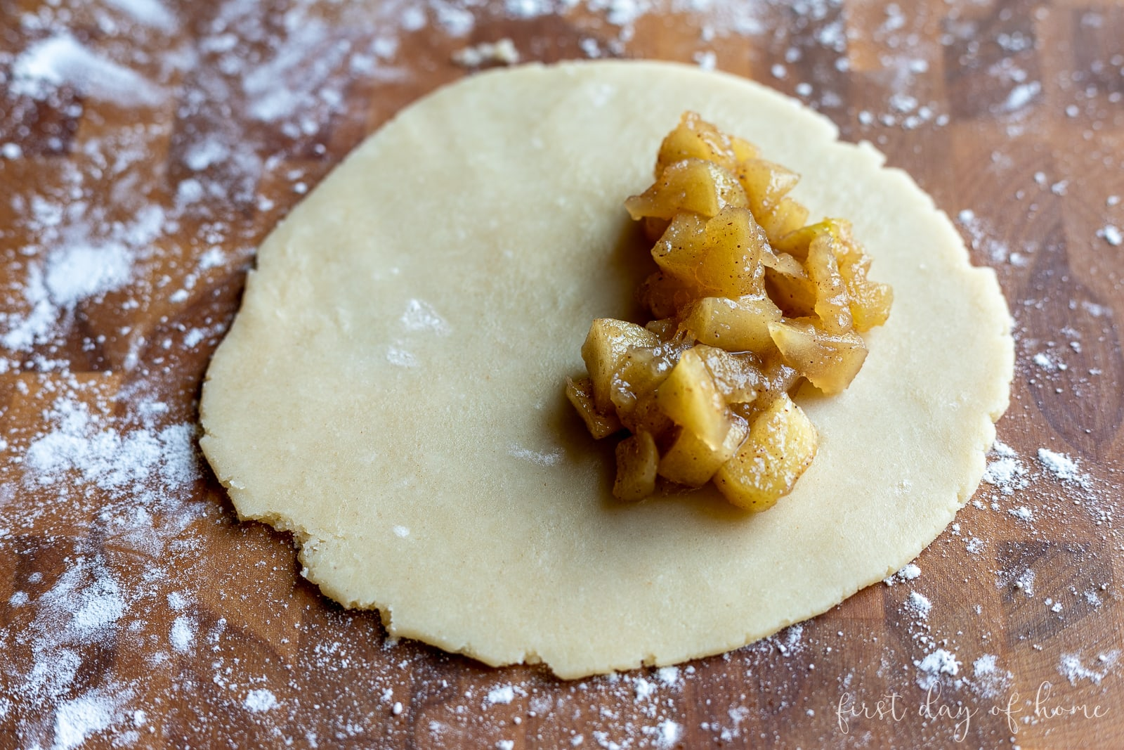 Apple filling on round empanada dough before pressing closed