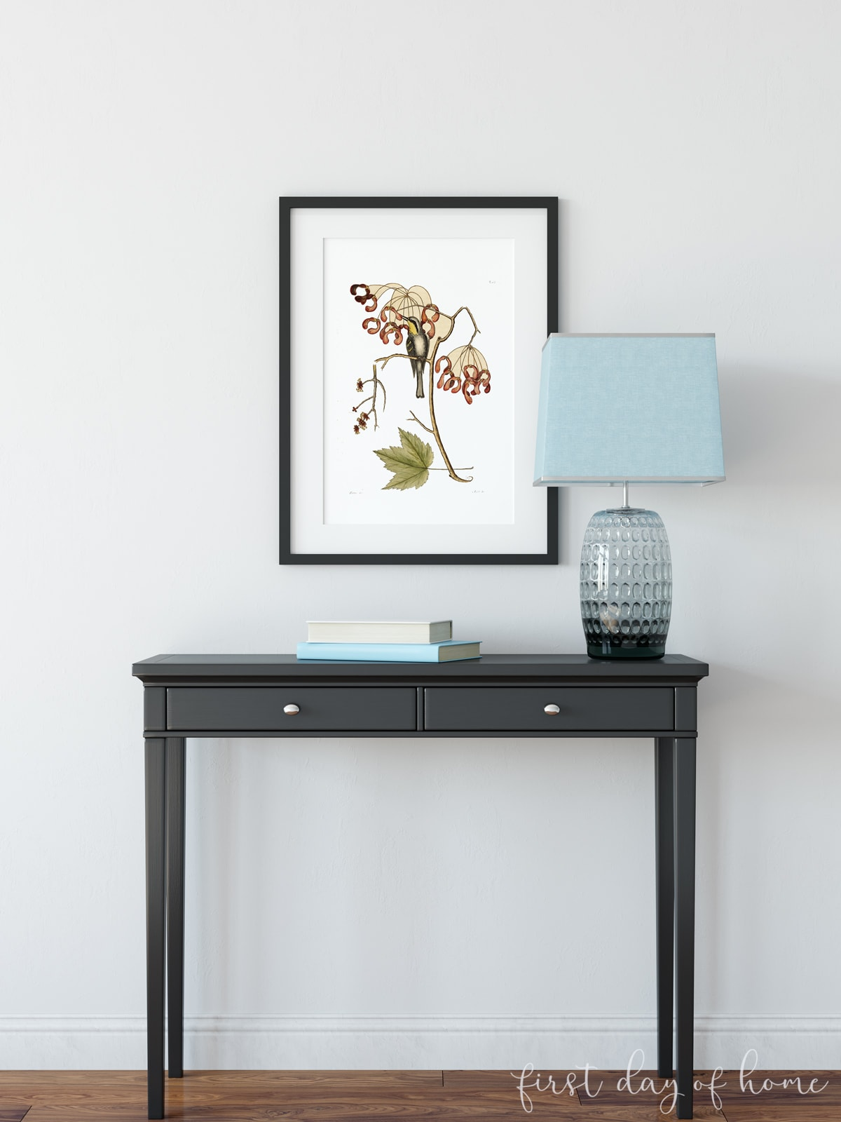 Vintage botanical art print hanging on wall above black desk with lamp and books
