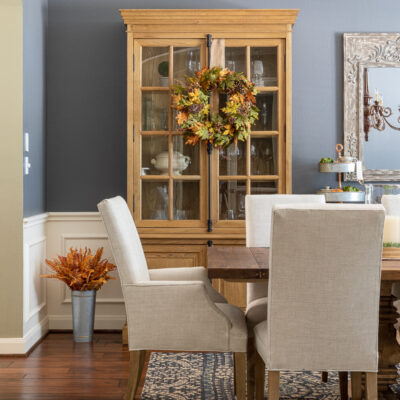 Fall home decor in formal dining room - wreath hanging on wooden cabinet