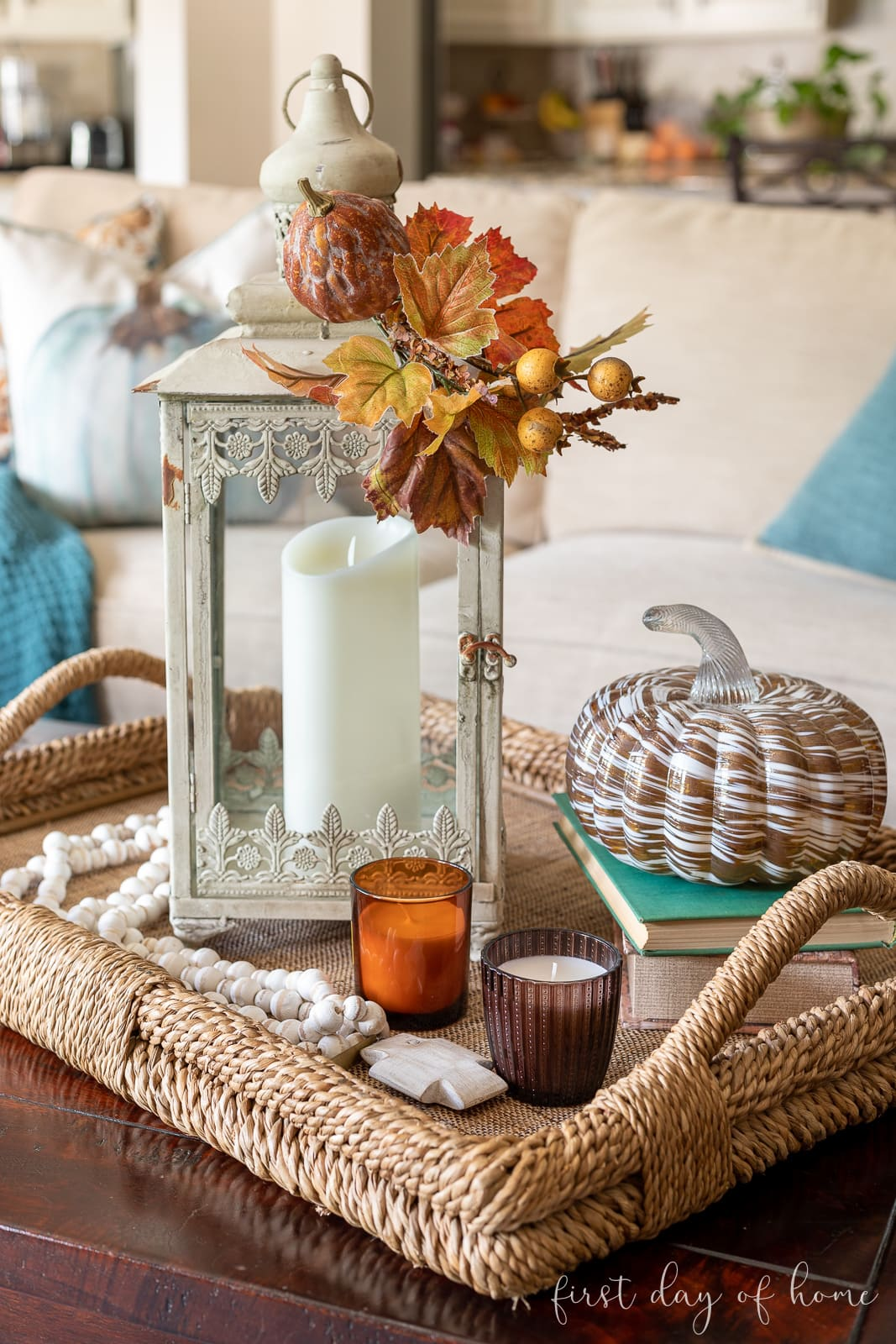 Fall centerpiece on coffee table with amber glass candles and glass pumpkin decor on books