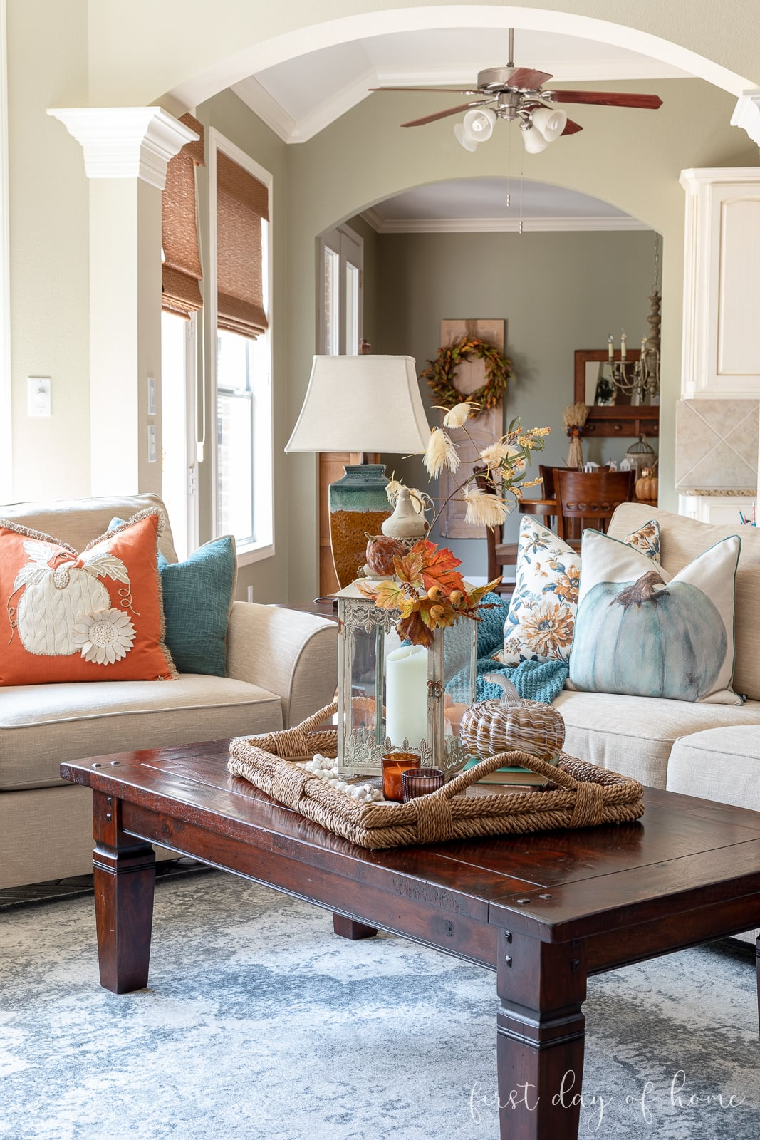Fall living room decor with orange and aqua throw pillows and fall centerpiece on coffee table