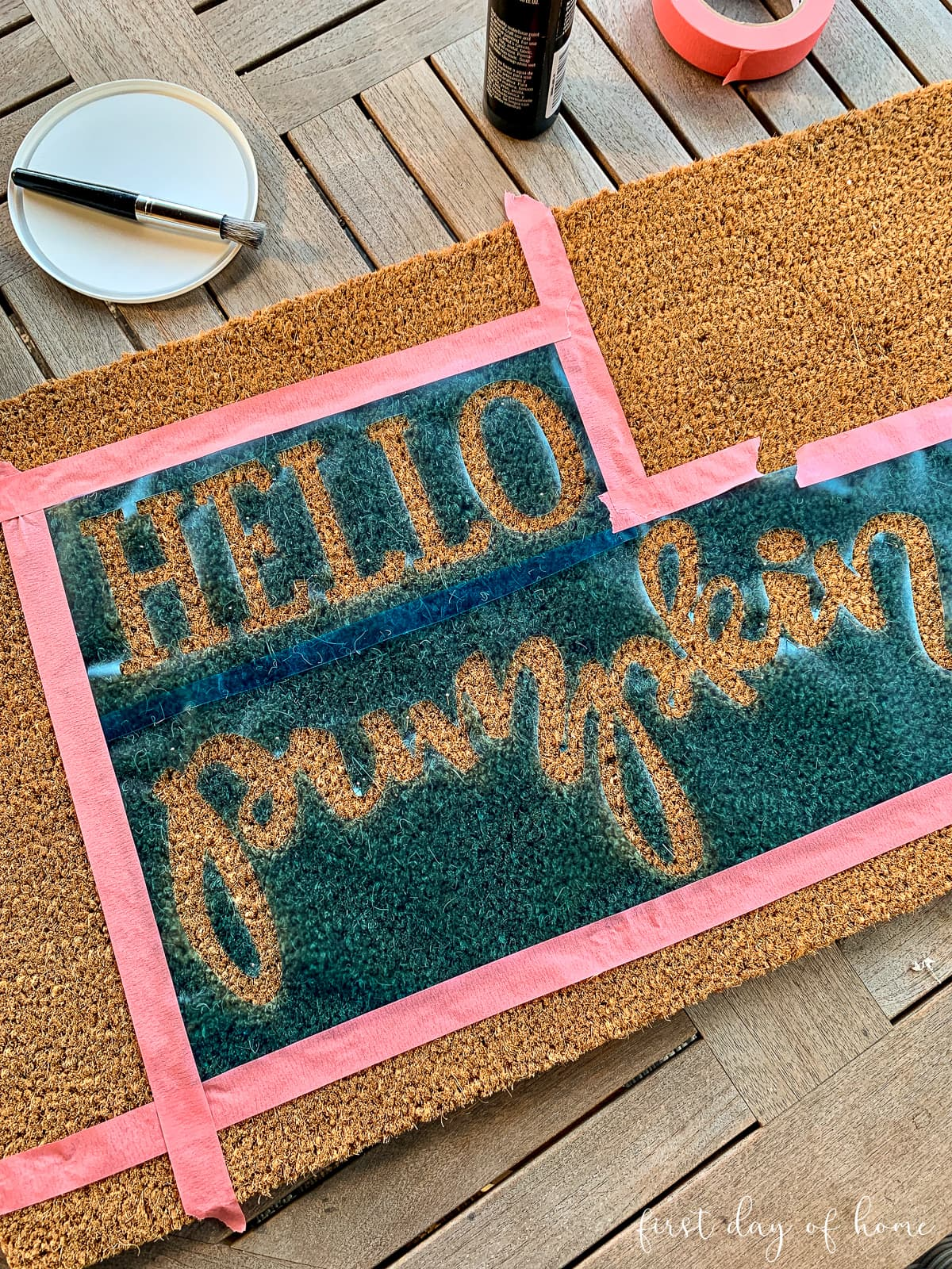 Applying the stencil to the coir doormat with pins and painter's tape