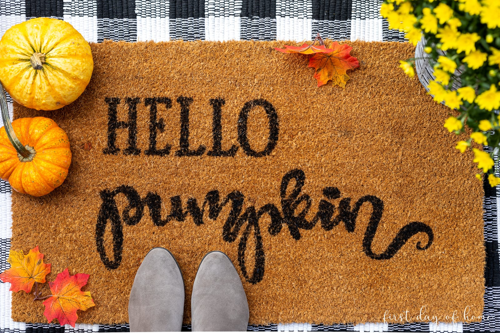 Hello Pumpkin coconut mat with black and white buffalo plaid rug layered underneath, surrounded by pumpkins and mums