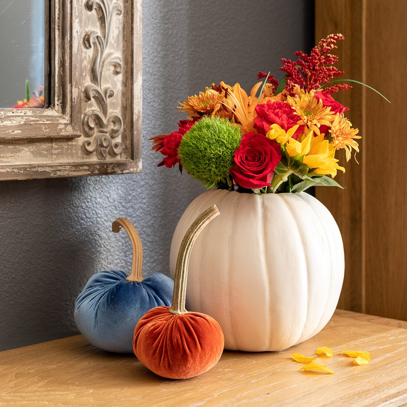 Pumpkin flower arrangement in white pumpkin with two velvet pumpkins sitting on sideboard table