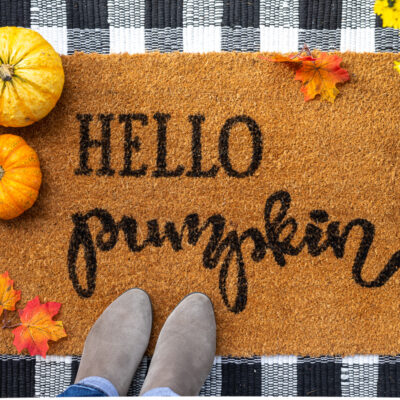 "Coco doormat on front porch with phrase ""Hello Pumpkin"" stenciled on it in black paint with buffalo plaid rug layered underneath"