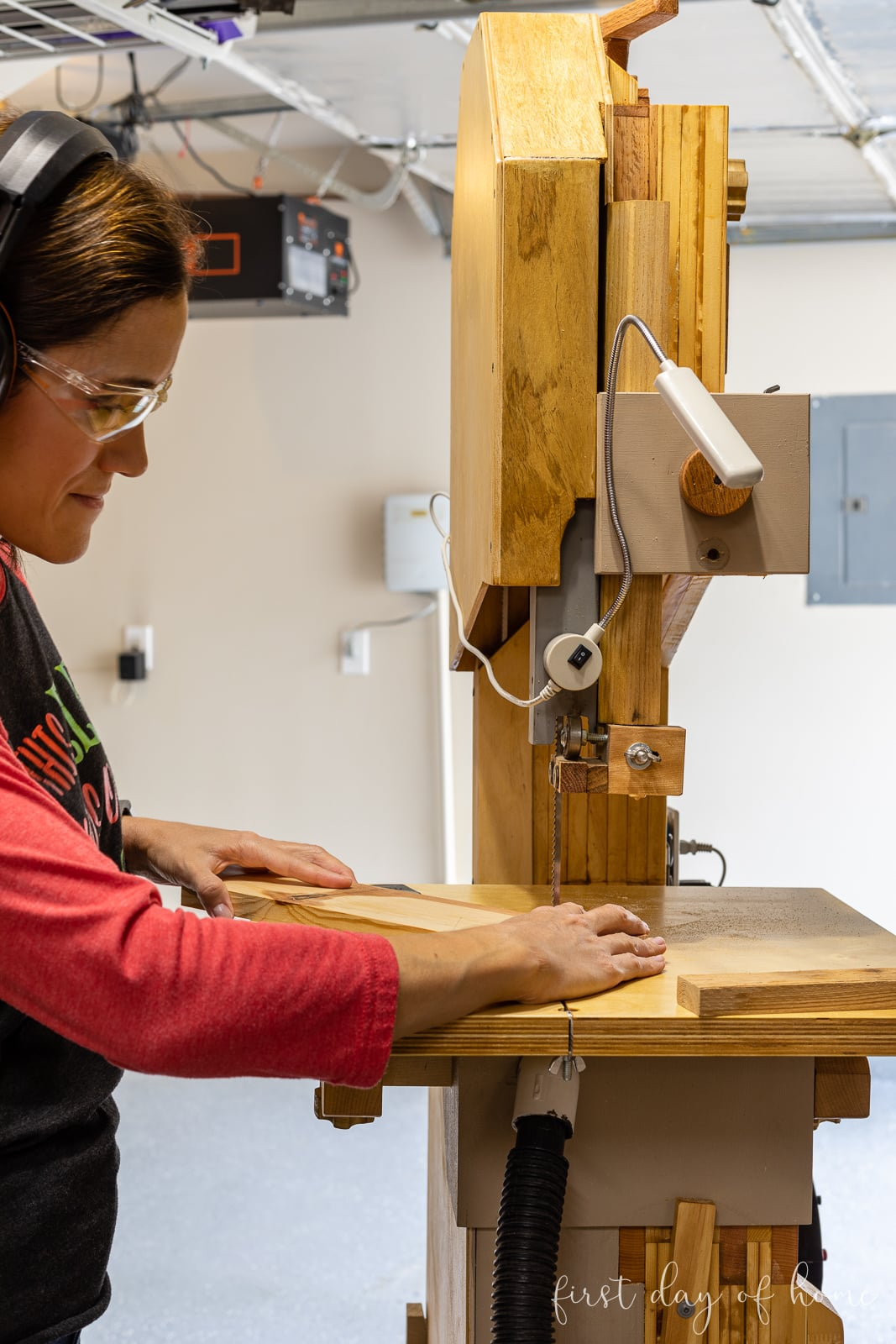 Crissy using a band saw to create wooden cutouts from scrap wood