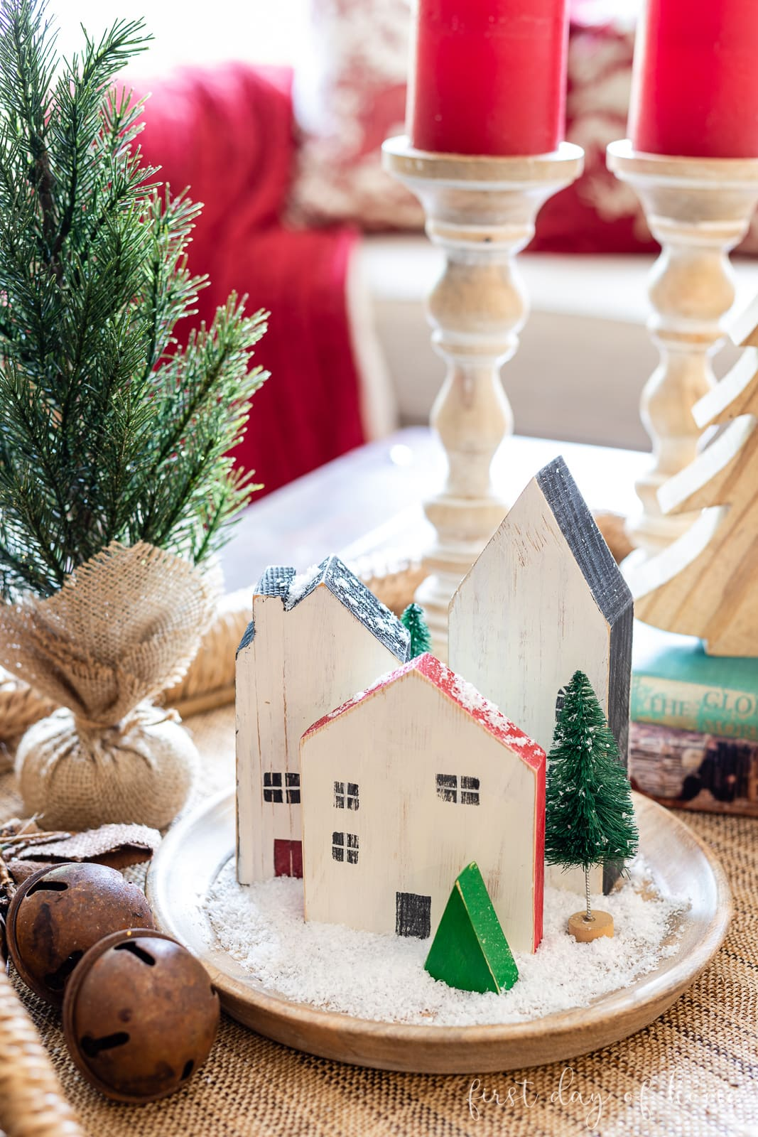 Three wooden craft houses sitting on coffee table tray with fake snow and bottle brush Christmas trees
