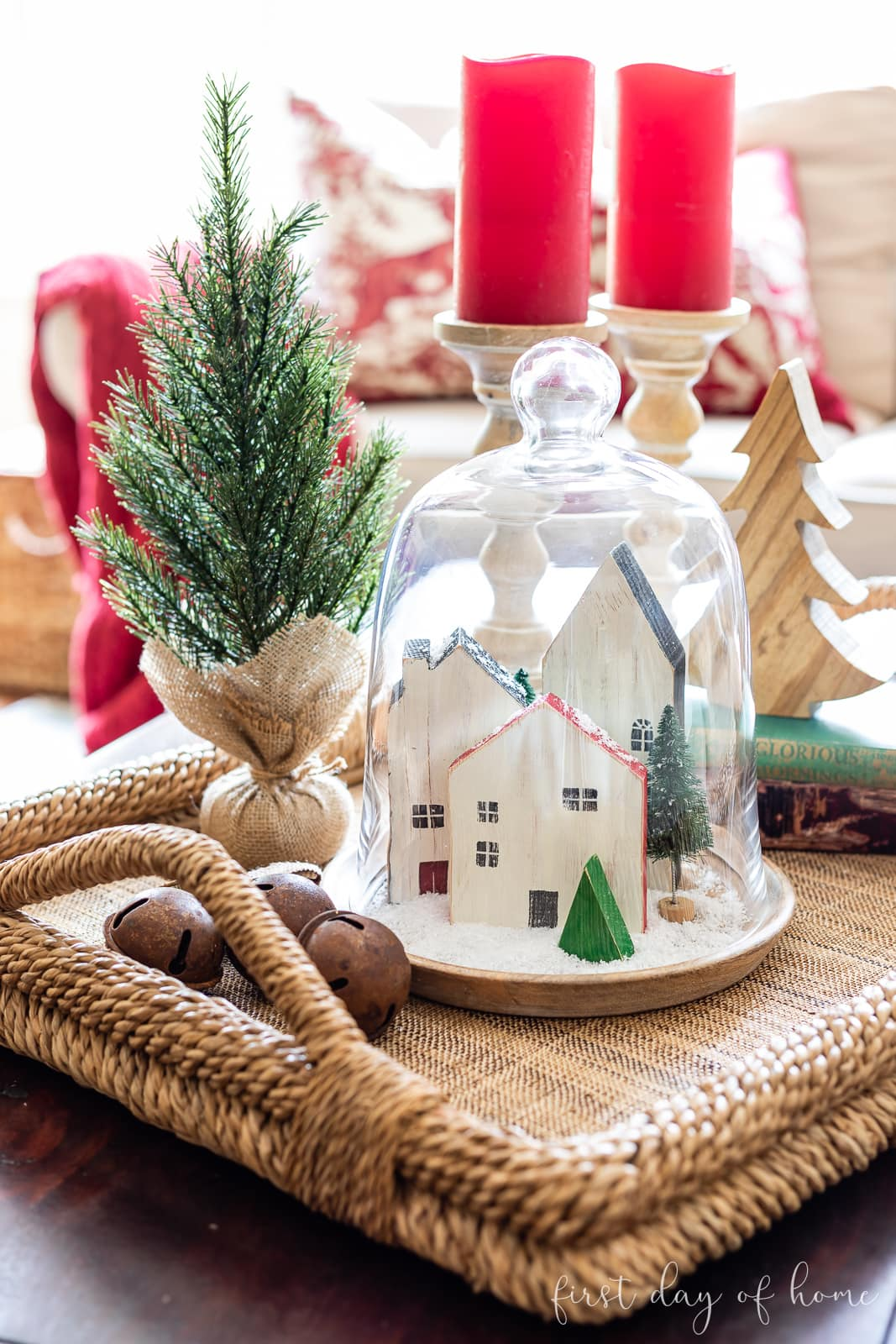 Christmas cloche with mini wooden houses and bottle brush trees on coffee table tray