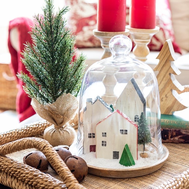 Mini wooden houses under a glass cloche with Christmas decor on a coffee table tray