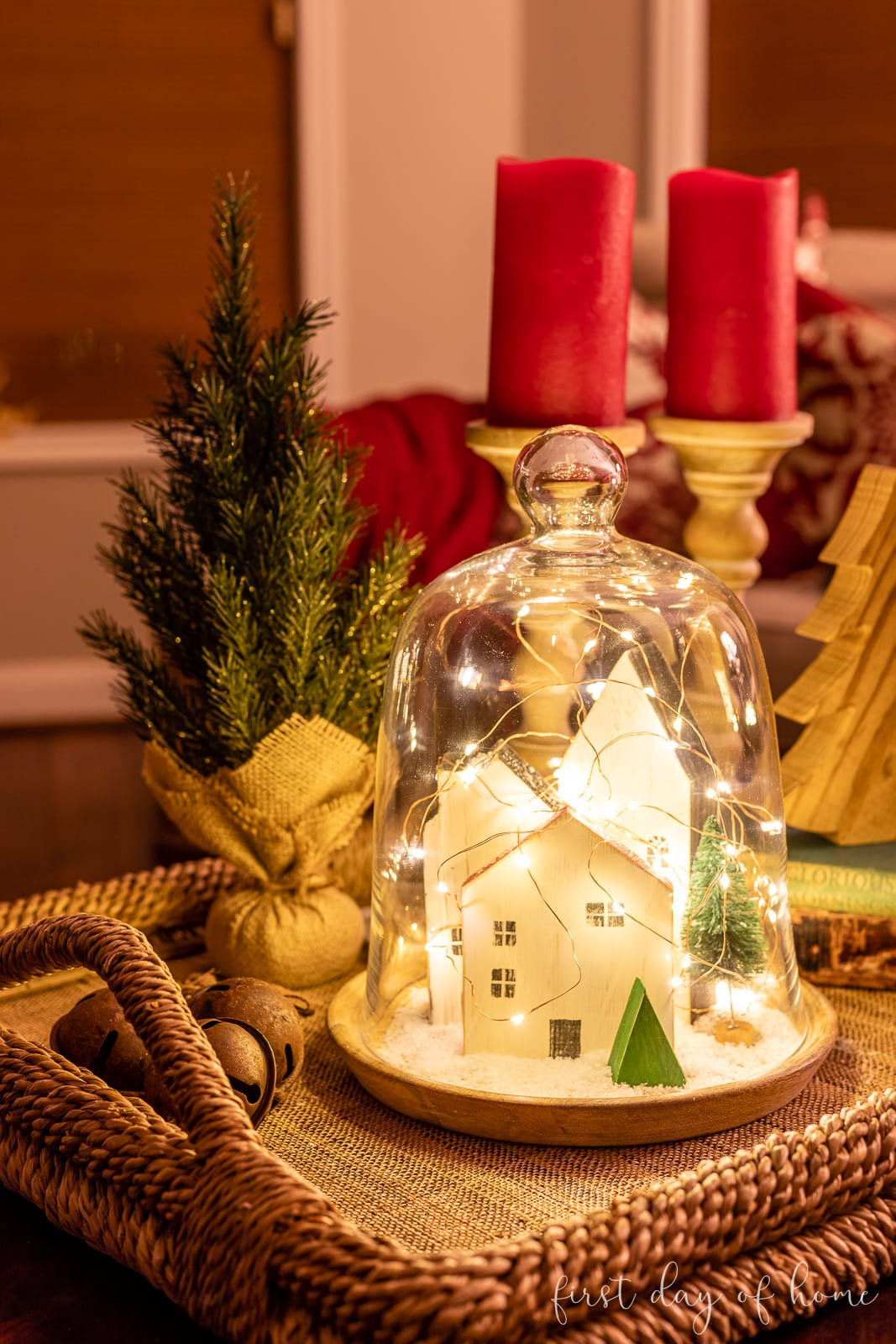 Christmas cloche at night with twinkle lights and trio of wood houses inside