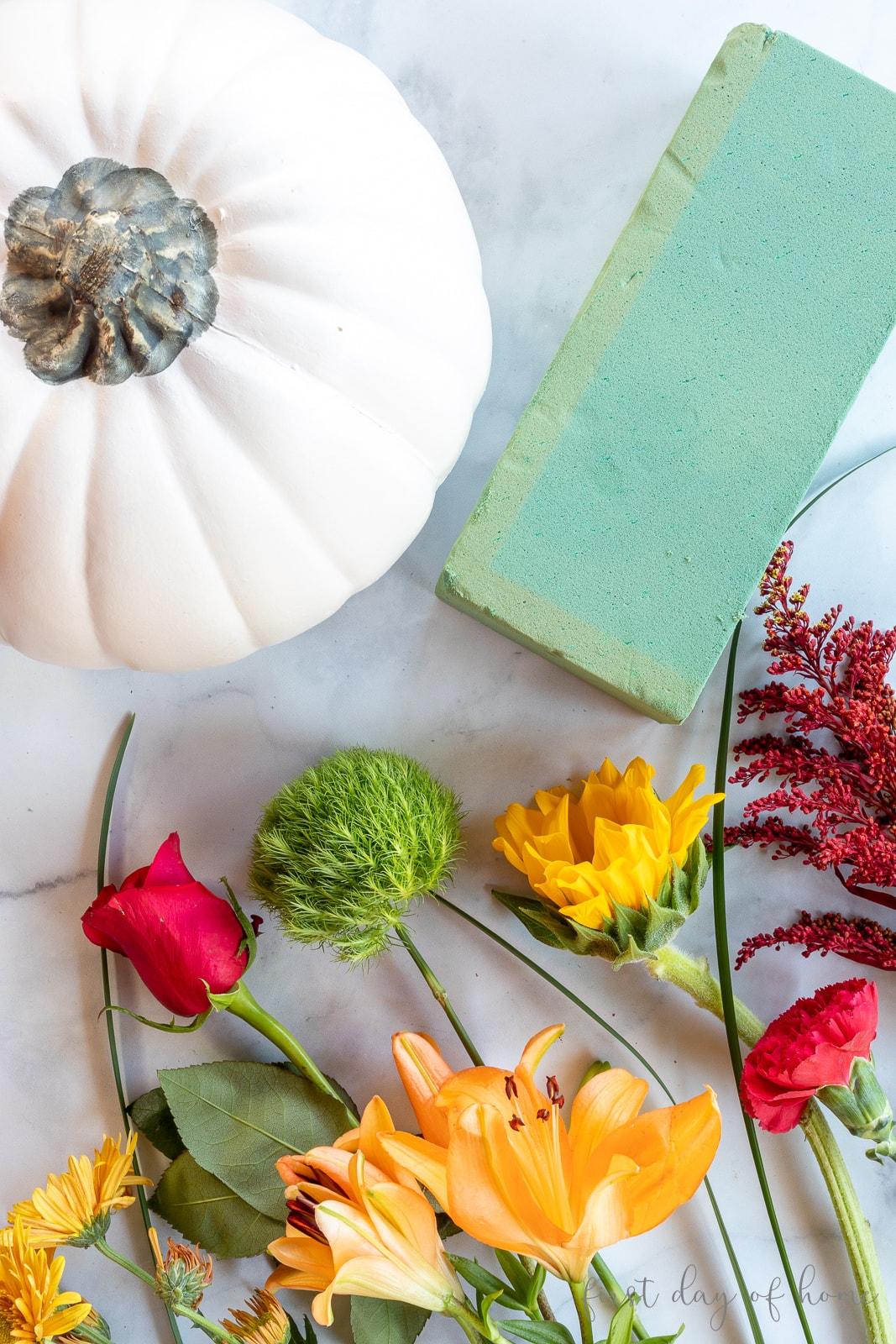 Supplies for faux pumpkin arrangement, including floral foam, fresh flowers and white faux pumpkin