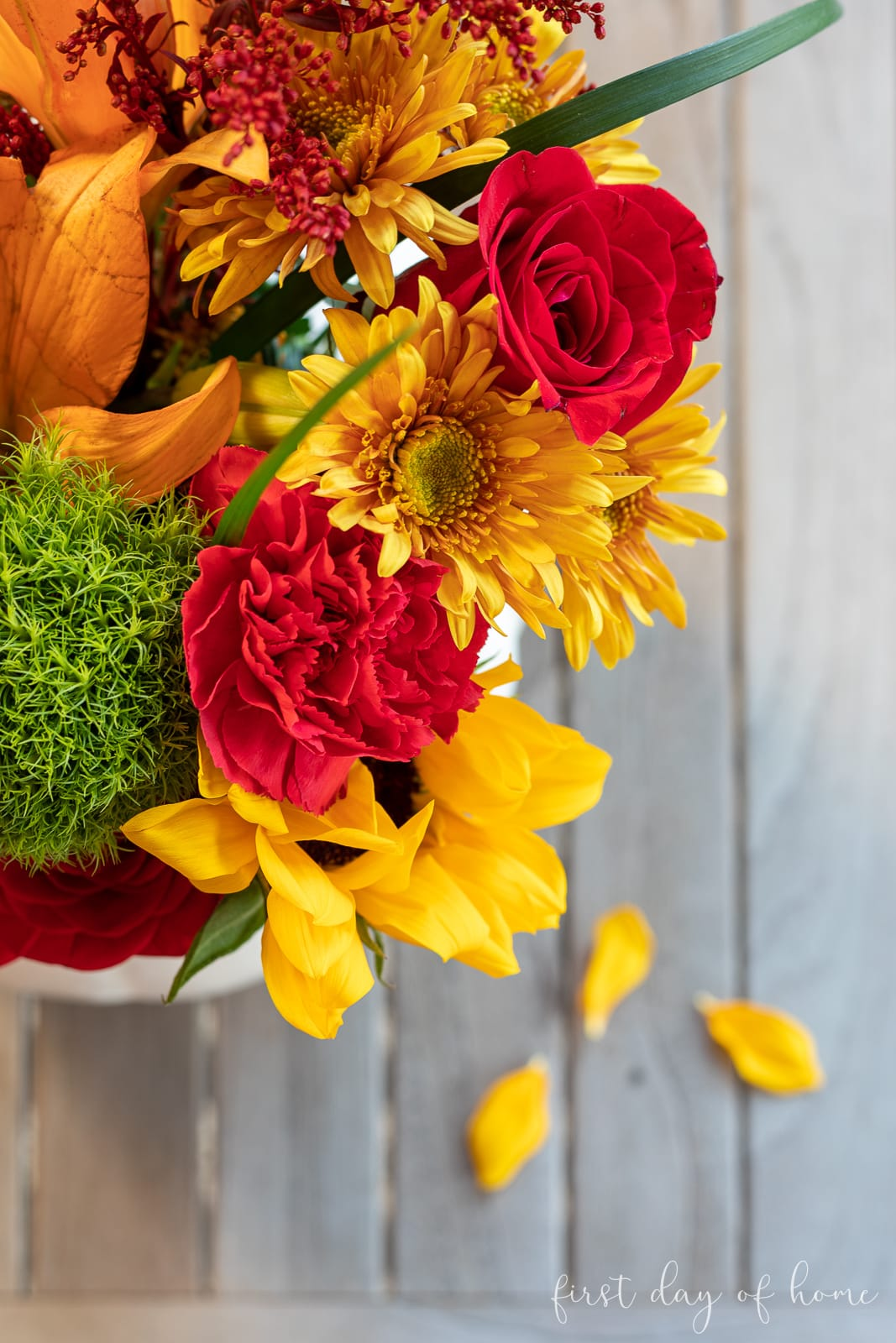 Bird's eye view of pumpkin flower arrangement with roses, carnations, sunflowers and other stems