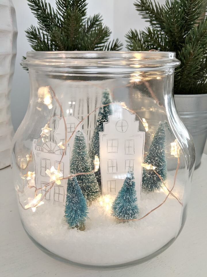 Christmas scene with bottle brush Christmas trees and paper house cutouts in a jar