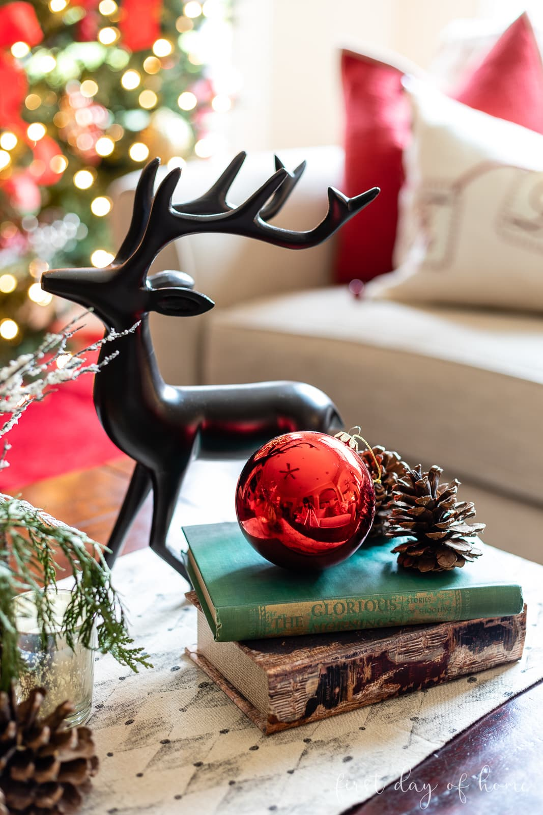 Bronze reindeer with books and red ball ornament next to pine cones