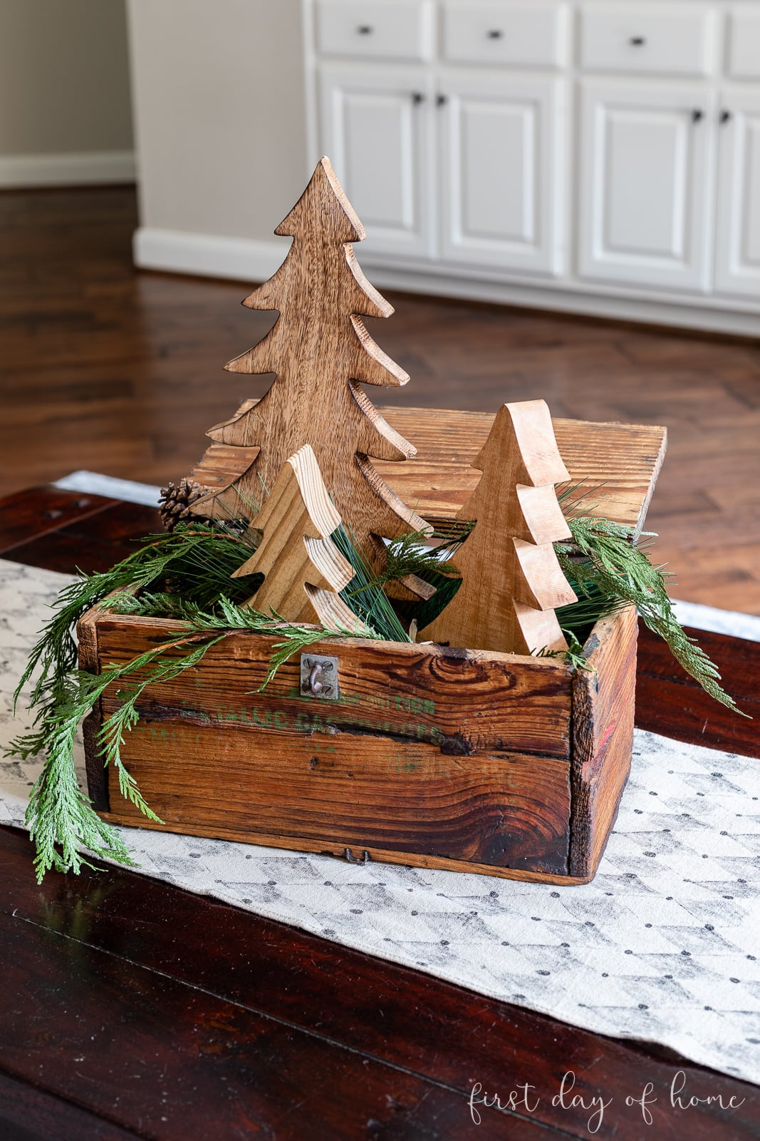 Wooden Christmas box filled with wooden trees and cedar garland