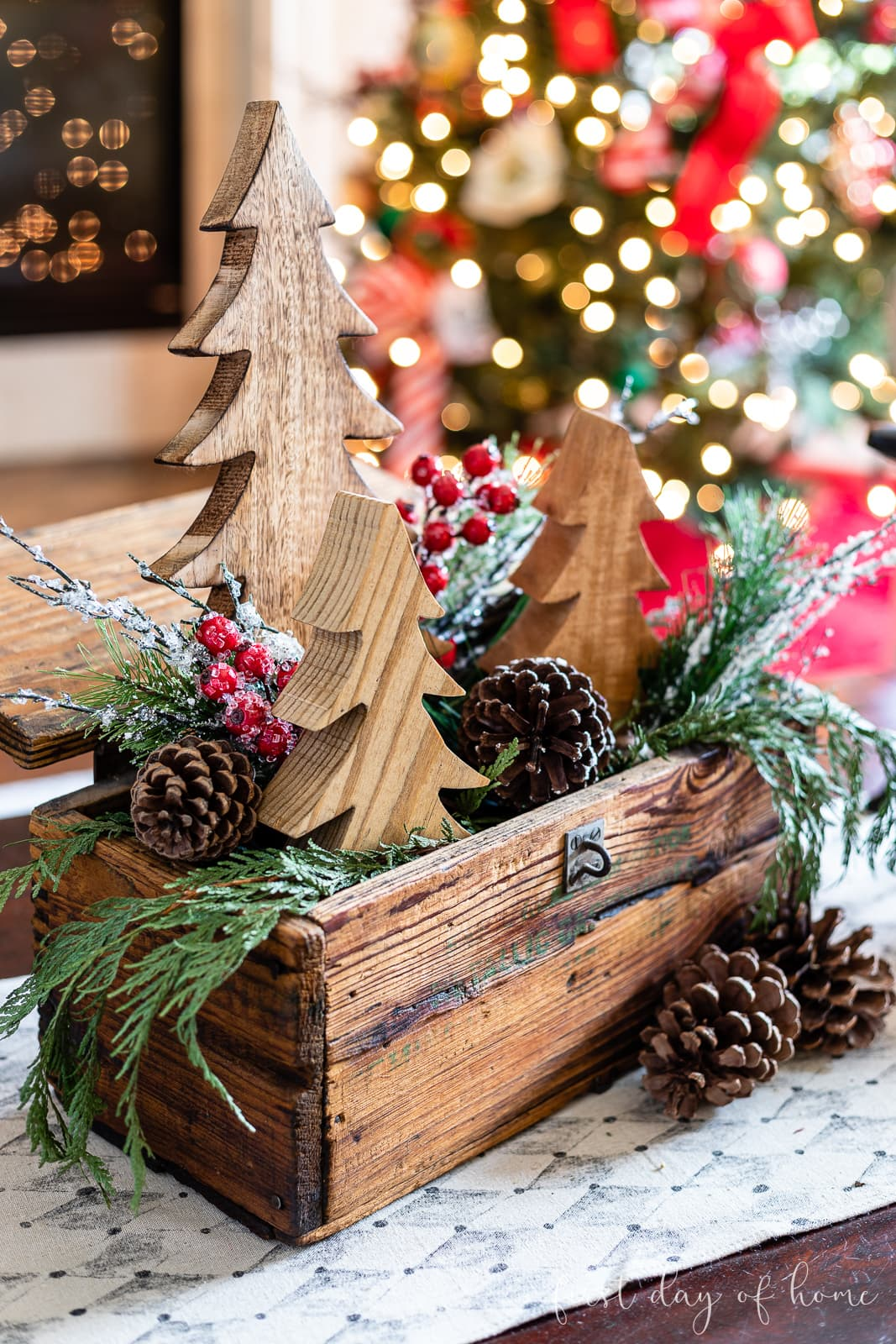Wooden crate decorated for Christmas with trio of wooden trees, real evergreen branches, pine cones and berries