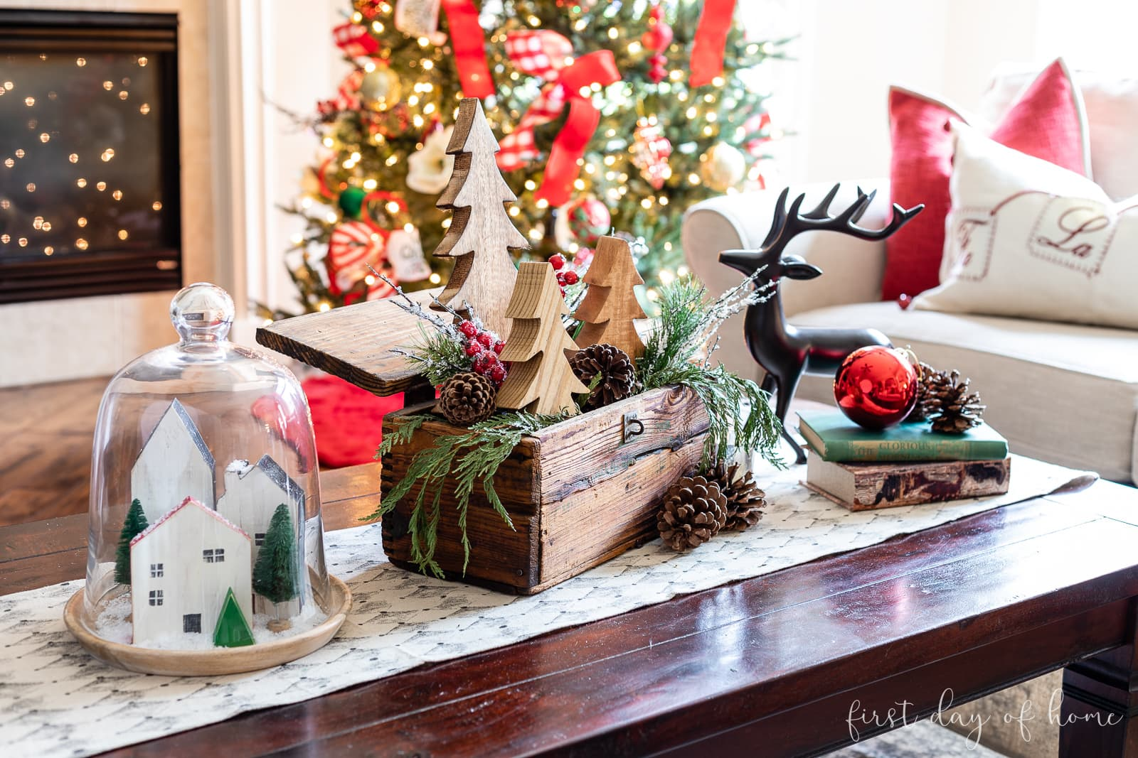Coffee table decorated for Christmas with cloche, crate decorated with trees, and reindeer with books
