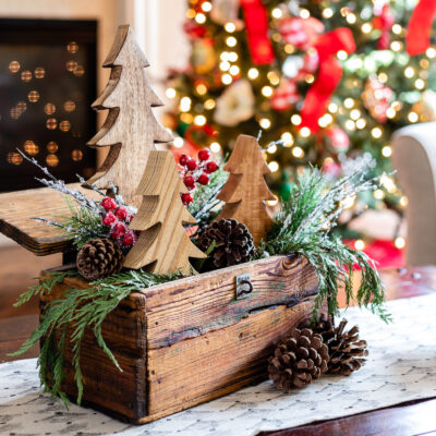 Christmas coffee table centerpiece with wooden Christmas trees and pine stems with berries in a rustic crate