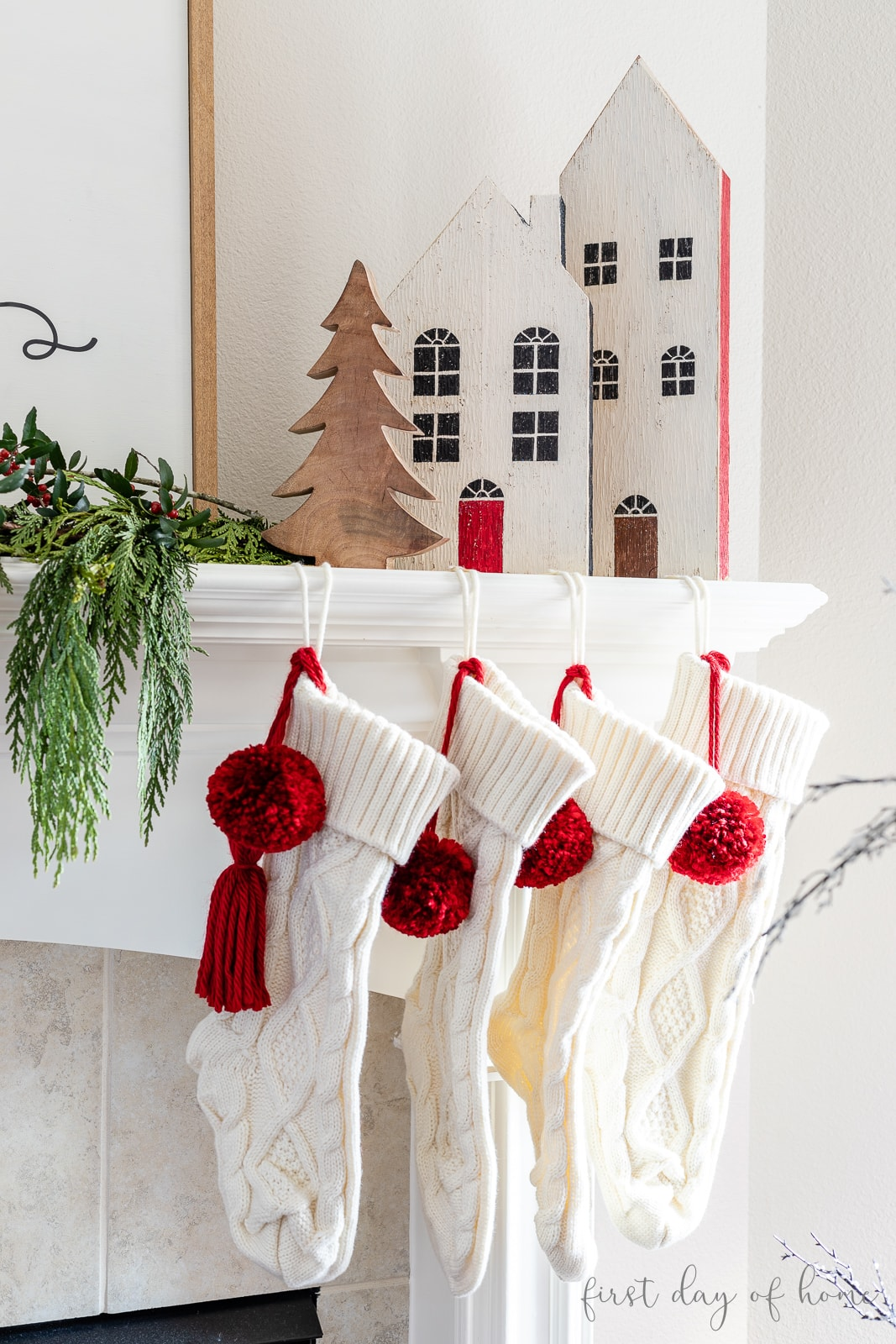Christmas mantel with knit stockings and two DIY wooden houses with a wooden Christmas tree