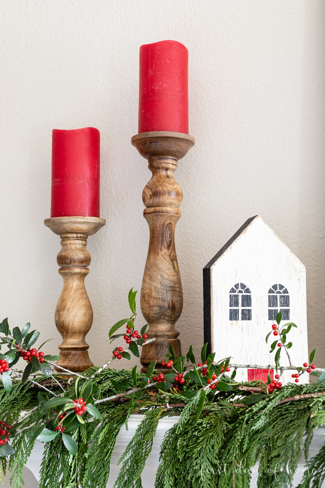 Two wooden candlesticks with red LED candles and a wooden house on mantel with real cedar garland