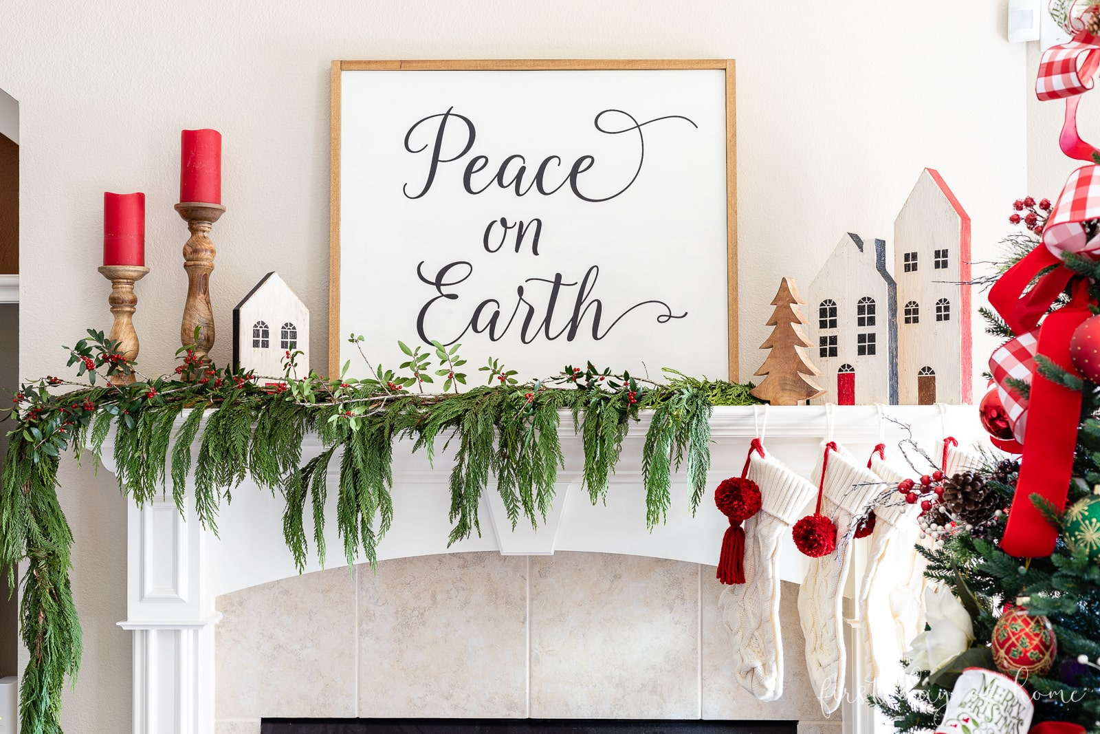 "Farmhouse Christmas mantel with DIY wooden sign that reads ""Peace on Earth"""