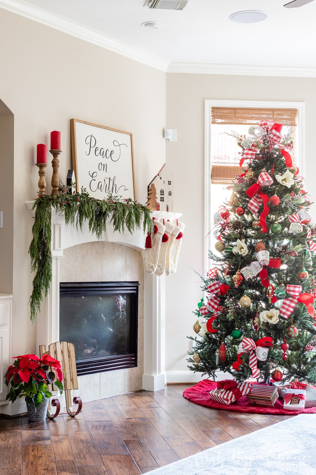 Christmas living room with red and green themed Christmas tree and farmhouse style mantel