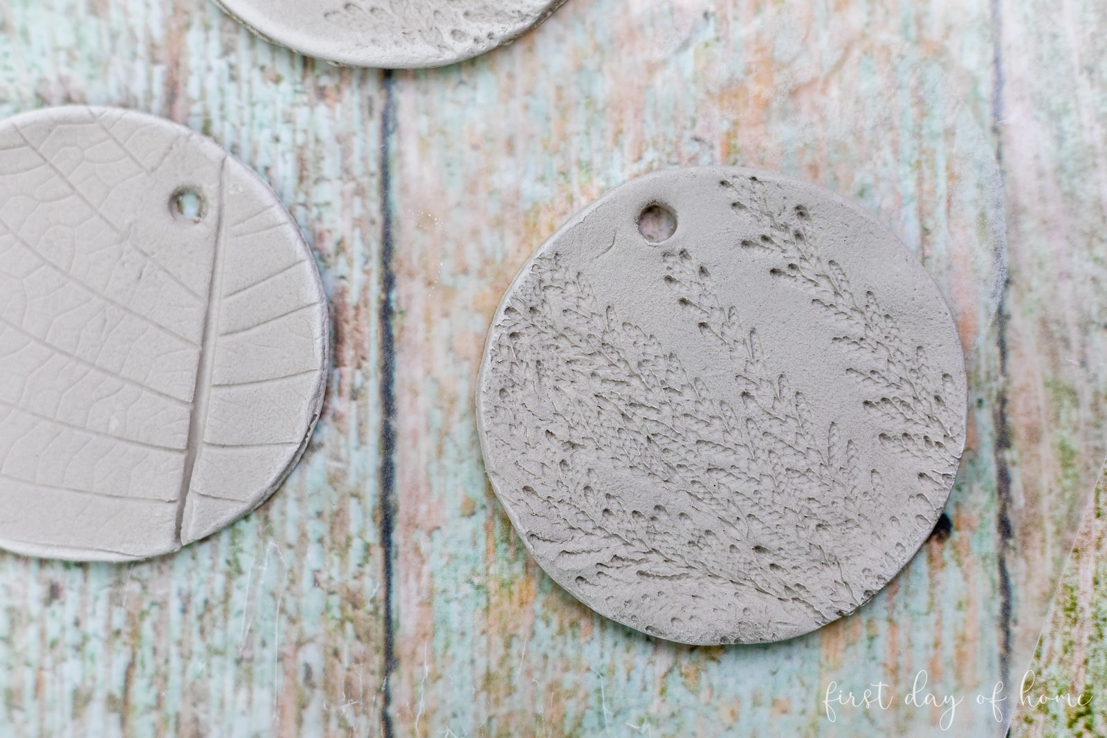 Round air dry clay ornament with imprint of cedar branch before drying