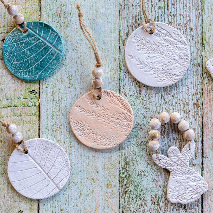 Air dry clay ornaments painted and texturized with natural stems in round and angel shapes