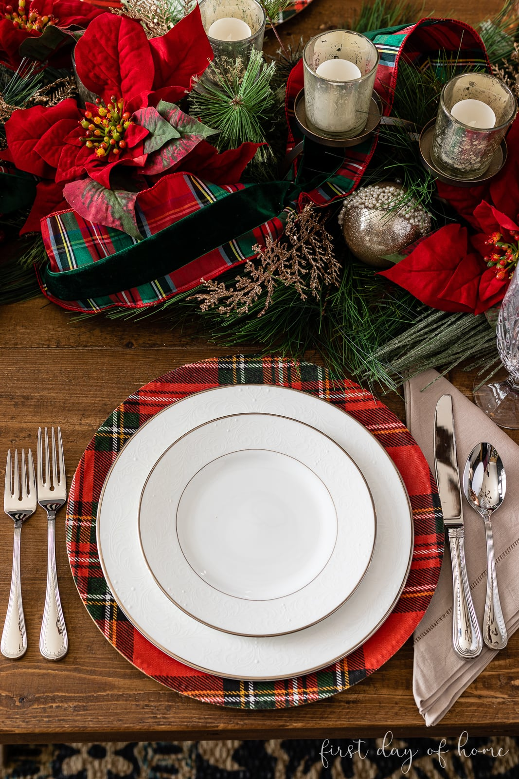 Christmas place setting with plaid charger plate and white china next to table centerpiece