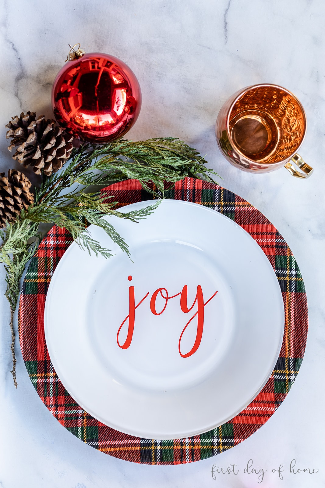 "Christmas plaid charger plate with white plate reading ""Joe"" on top, alongside a copper mug and Christmas accents"
